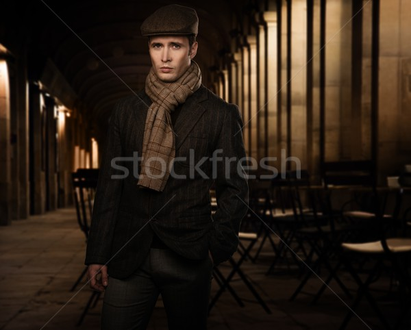 Young man in brown jacket wearing cap and scarf alone outdoors at night   Stock photo © Nejron