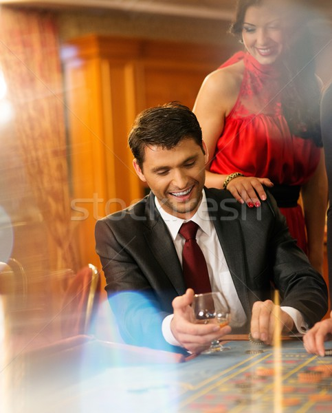 Beautiful young couple behind roulette table in a casino Stock photo © Nejron