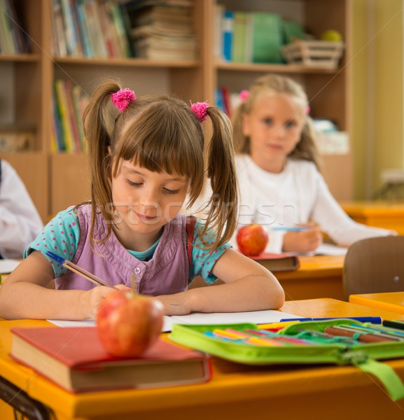 Little schoolgirl sitting behind school desk during lesson in school Stock photo © Nejron