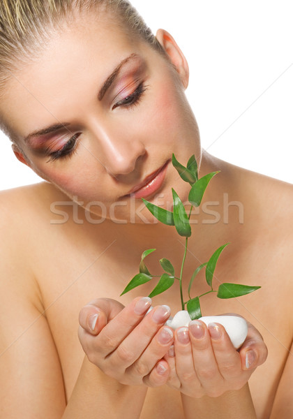Beautiful blond girl holding young plant growing up through ston Stock photo © Nejron