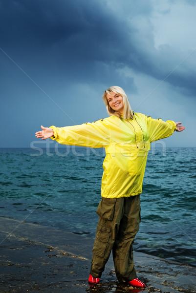 Jeune femme jaune imperméable océan tempête femme Photo stock © Nejron