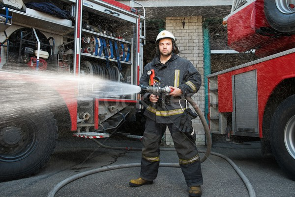 Firefighter holding water hose near truck with equipment  Stock photo © Nejron