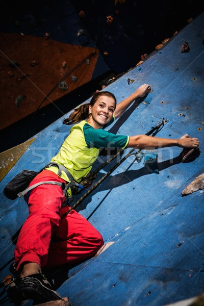 Young woman practicing rock-climbing on a rock wall indoors Stock photo © Nejron