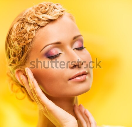 Beautiful young woman with hairdo touching her face with hand Stock photo © Nejron