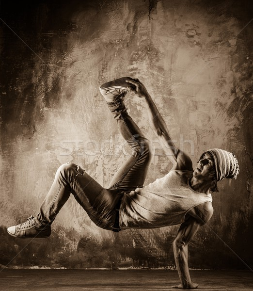 Toned picture of young man  doing acrobatic movements against grunge wall Stock photo © Nejron