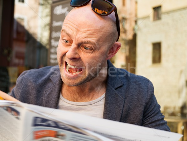 MIddle-aged man becoming enraged while reading newspaper outdoors Stock photo © Nejron