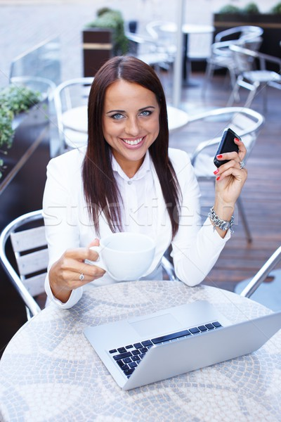 Smiling young brunette woman alone with laptop and mobile phone in summer cafe Stock photo © Nejron