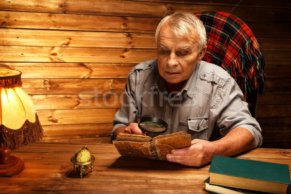 Senior man with magnifier reading vintage book in homely wooden interior  Stock photo © Nejron