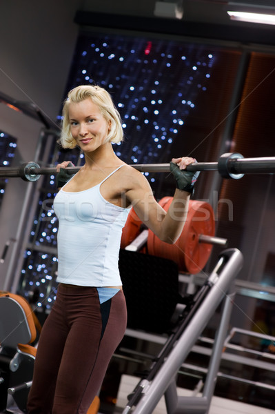 Strong beautiful woman lifting heavy weights Stock photo © Nejron