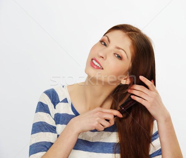 Beautiful brunette woman brushing her hairs Stock photo © Nejron