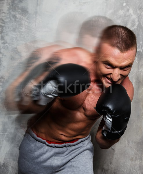 Young sporty man in boxing gloves in motion Stock photo © Nejron