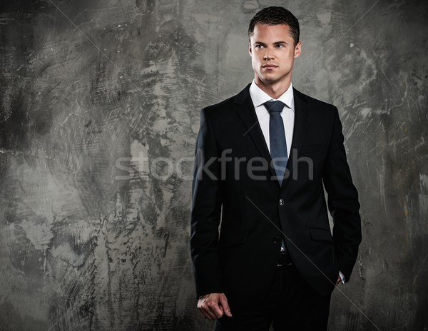 Well-dressed man in black suit against grunge wall  Stock photo © Nejron