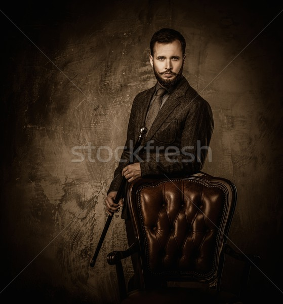 Handsome well-dressed man with stick standing near leather chair  Stock photo © Nejron
