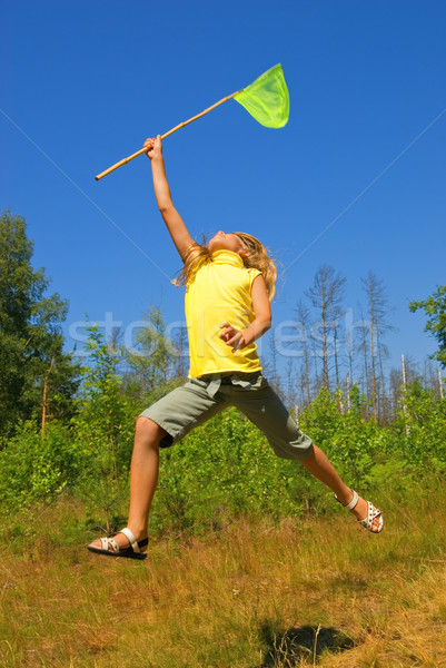 Young girl with butterfly net jumping on a meadow Stock photo © Nejron