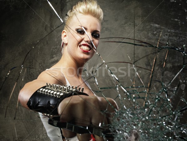 Punk girl breaking glass with a brass knuckles Stock photo © Nejron