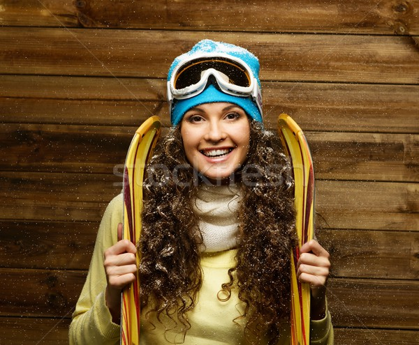 Smiling woman with skies standing against wooden house wall under snow Stock photo © Nejron