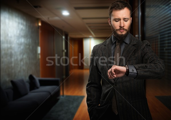 Handsome well-dressed man with beard looking at his wrist watch in a hallway Stock photo © Nejron