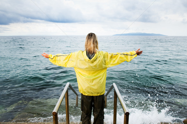 Brave woman greeting stormy ocean Stock photo © Nejron