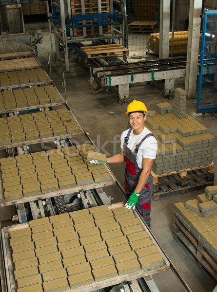 Young worker near conveyor belt with paving stone  on a factory   Stock photo © Nejron
