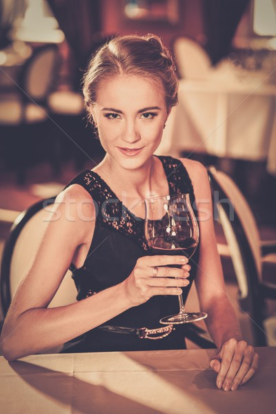 Beautiful young girl with glass of red wine alone in a restaurant Stock photo © Nejron