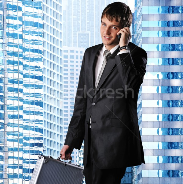 Young businessman against his office building Stock photo © Nejron