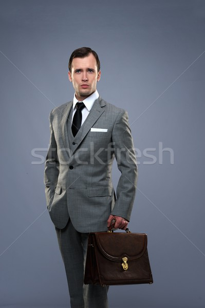 Businessman with a briefcase isolated on grey Stock photo © Nejron