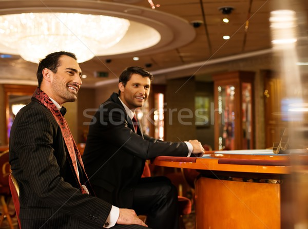 Two young men in suits behind table in a casino Stock photo © Nejron