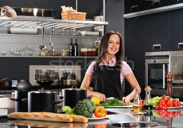 Cheerful young woman in apron on modern kitchen cutting vegetables Stock photo © Nejron