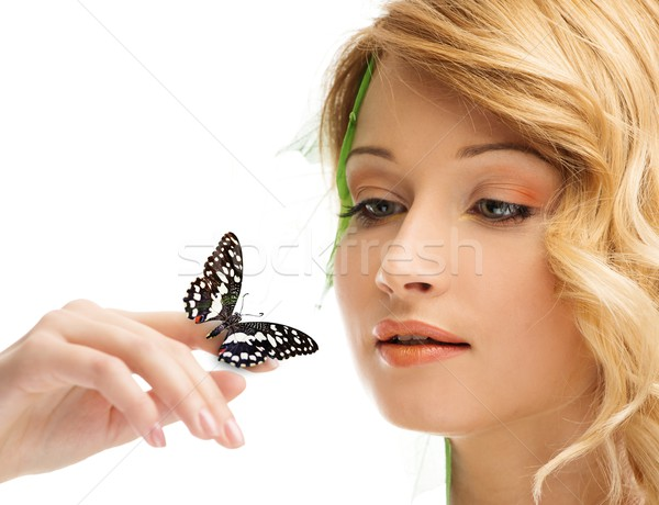 Dreaming young woman in conceptual spring costume with butterfly on her hand  Stock photo © Nejron