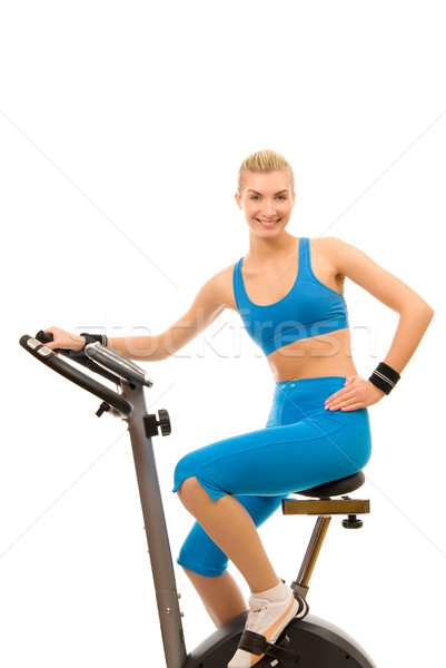 Stock photo: Beautiful young woman on exercise bicycle over white background