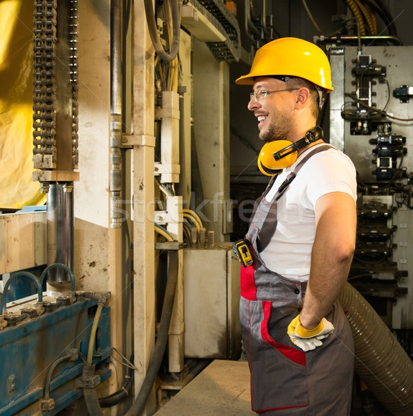 Cheerful worker in safety hat near machine on a factory Stock photo © Nejron