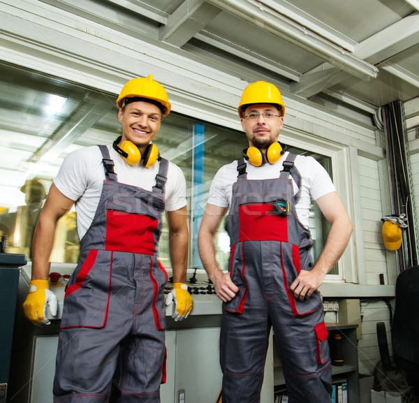 Two workers wearing safety hat in a factory control room Stock photo © Nejron
