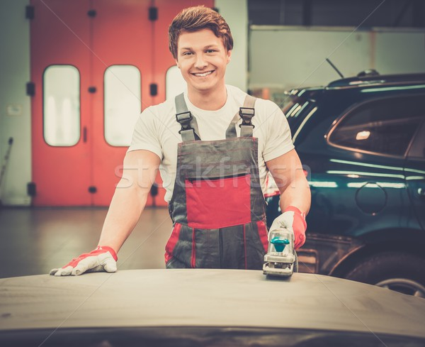Young serviceman performing grinding with machine on a car bonnet in a workshop Stock photo © Nejron