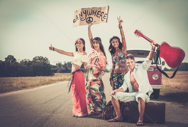 Multi-ethnic hippie hitchhikers with guitar and luggage on a road Stock photo © Nejron
