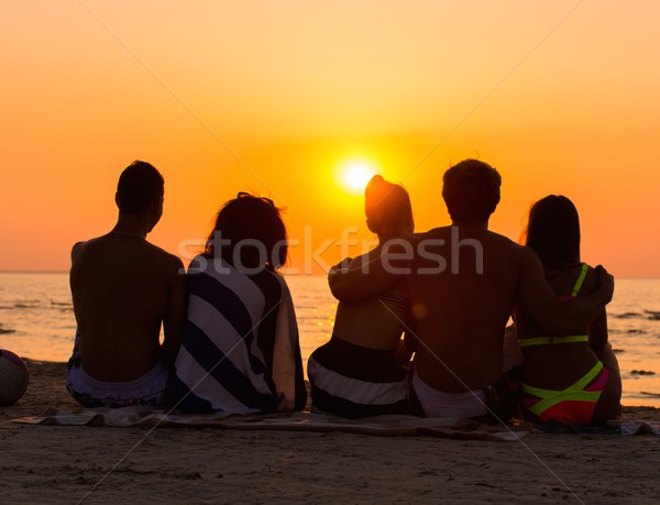 Silhouettes a young people sitting on a beach looking at  sunset  Stock photo © Nejron