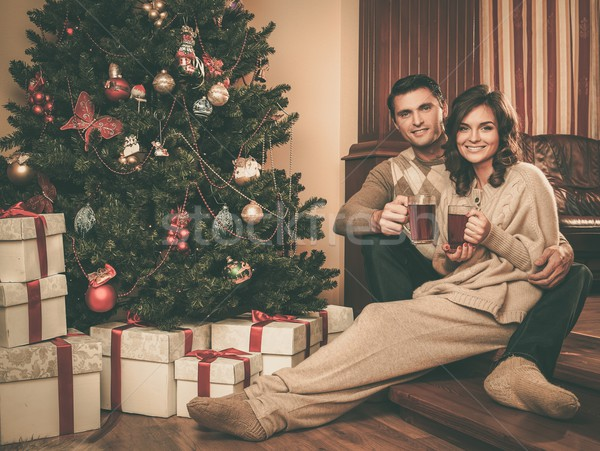 Couple with cups of hot drink near Christmas tree Stock photo © Nejron
