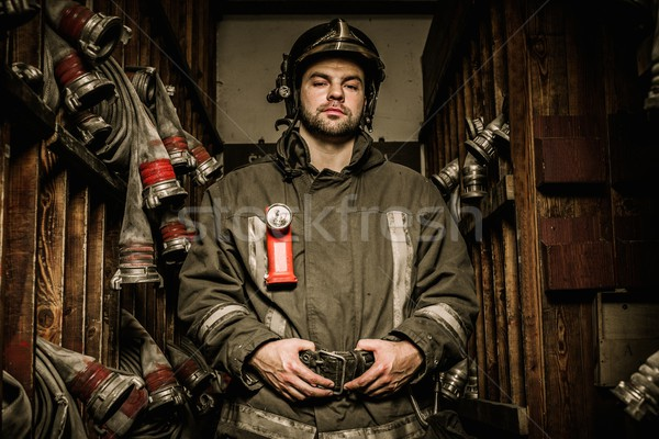 Firefighter in storage room with fire hoses  Stock photo © Nejron