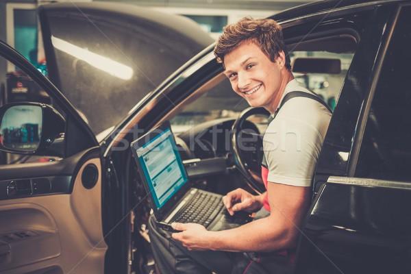 Serviceman making car diagnostics with laptop in a workshop Stock photo © Nejron