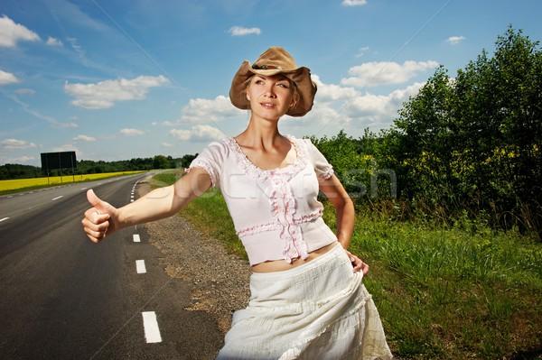 Hitchhiker girl in cowboy hat. Stock photo © Nejron