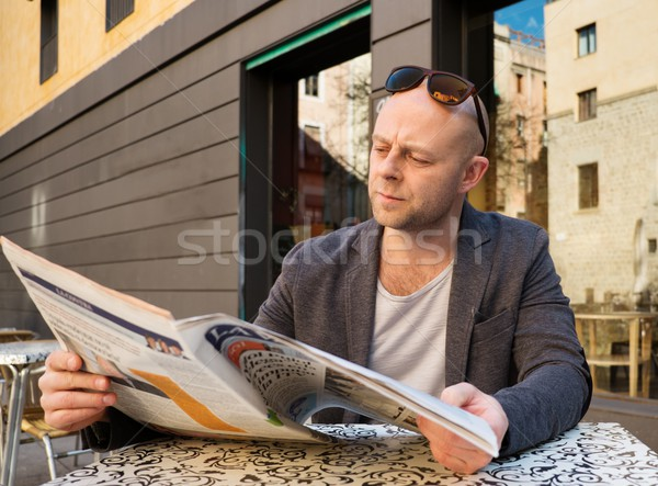MIddle-aged man reading newspaper behind table in street cafe Stock photo © Nejron
