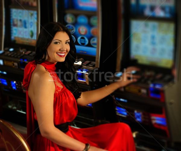 Stock photo: Beautiful woman in red dress playing slot machine