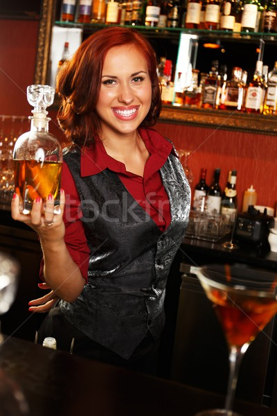 Beautiful redhead barmaid with bottle behind bar counter  Stock photo © Nejron