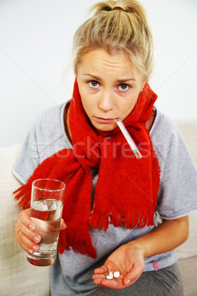 Sick young blond woman with pills, thermometer, and glass of water Stock photo © Nejron