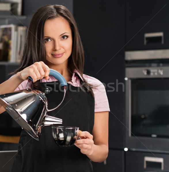 Cheerful young woman in apron on modern kitchen pouring hot drink in a cup Stock photo © Nejron