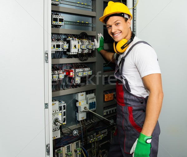 Cheerful electrician in a safety hat on a factory Stock photo © Nejron