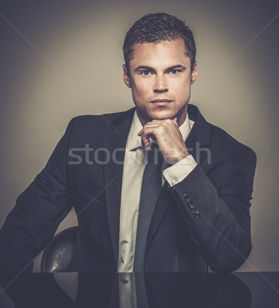 Handsome young well-dressed man in jacket  behind table  Stock photo © Nejron