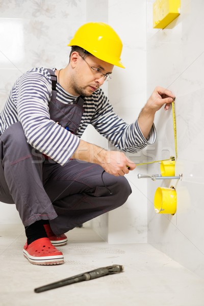 Builder measuring pipe in a bathroom  Stock photo © Nejron
