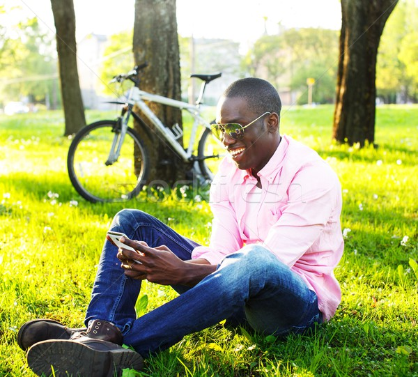 Young happy smiling african american with mobile phone and bicycle behind him in a park Stock photo © Nejron