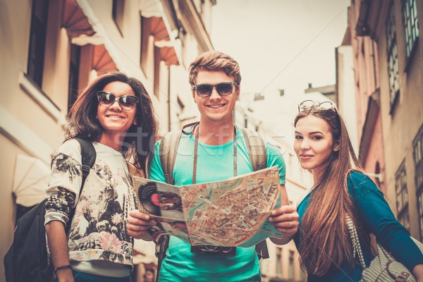 Multi ethnic friends tourists with map in old city  Stock photo © Nejron