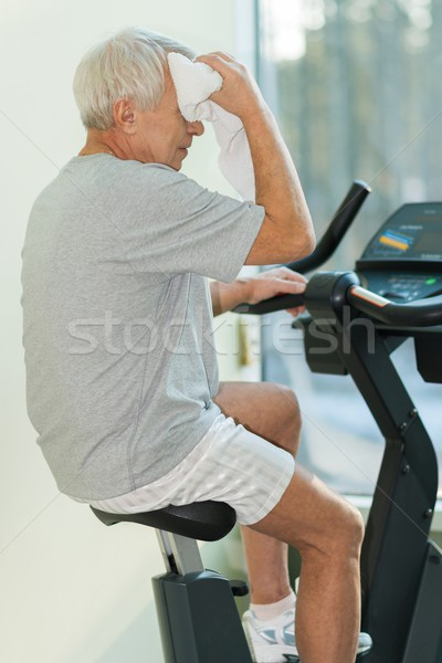 Stock photo: Tired senior man with towel on exercise bike in fitness club